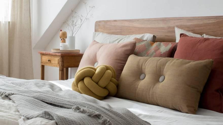 chambre cocooning comme mode de vie avec lit, coussins, tête de lit, plaid, table de chevet et rideaux.